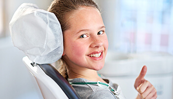 Young girl giving thumbs up in dental chair