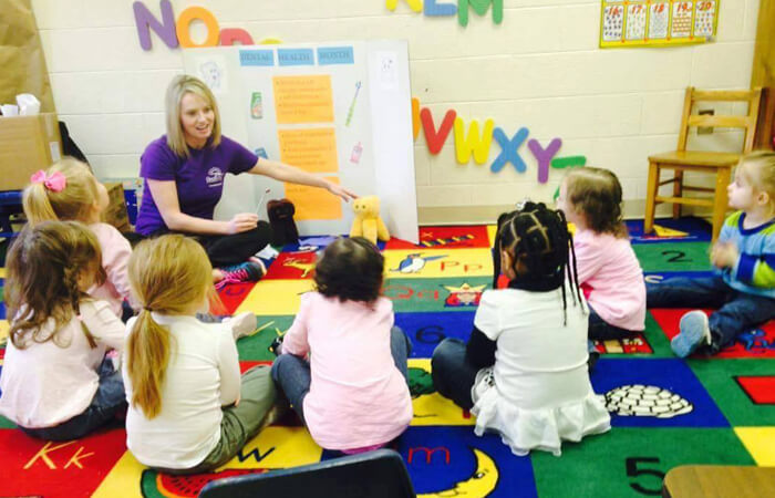 Smiles for Schools volunteer teaching small group of kids