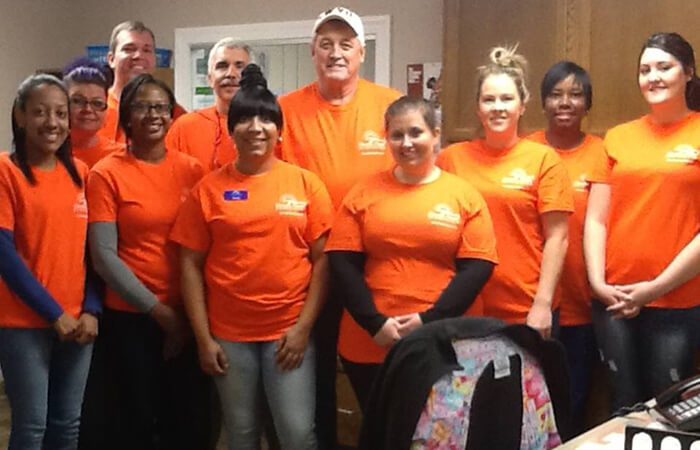 Dentists and their team of dental volunteers in orange shirts