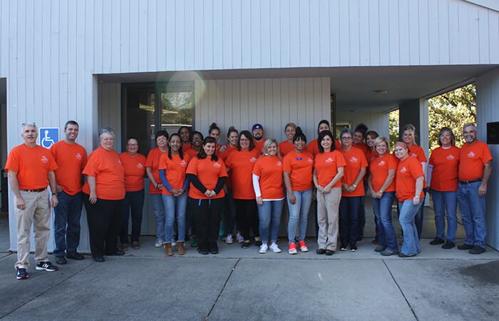 Full volunteer team photo in orange shirts