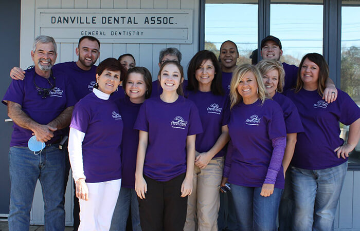 Team photo of dental volunteers in their purple T-shirts