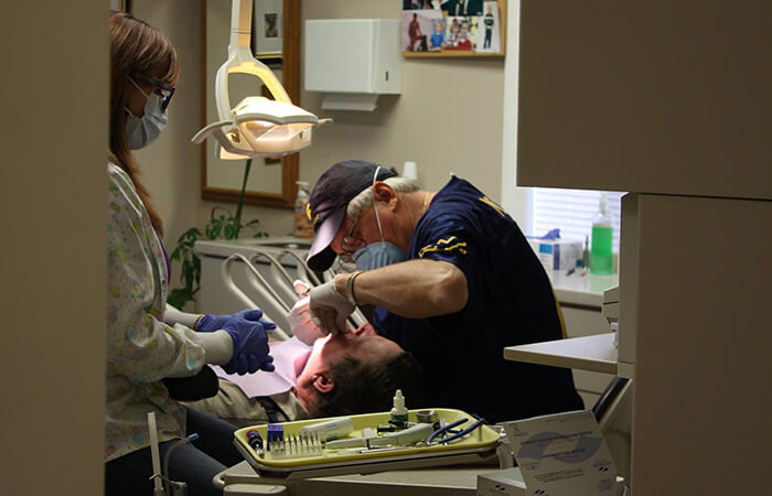 Dr. Payne working on male patient's teeth
