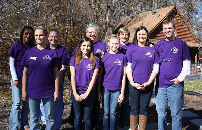 Dr. Payne smiling for a photo with kids in their purple T-shirts