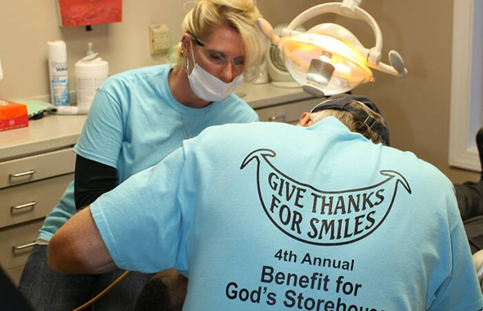 Dental volunteers in their teal shirts helping patients