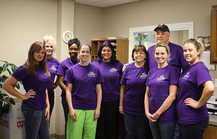 Dr. Evans and his dental volunteers pose in their purple T-shirts