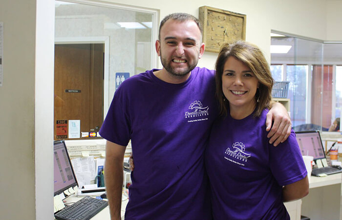 Two dental volunteers smiling in purple T-shirts