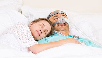 Woman sleeping next to man with CPAP