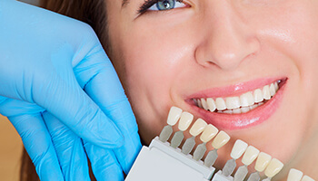 Chatham Teeth Whitening woman using tooth coloring tool