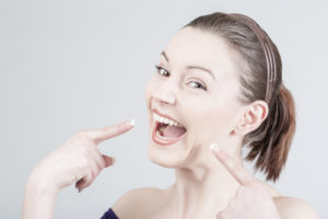 woman pointing at teeth