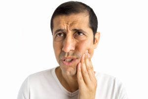 man holds jaw painfully from toothache