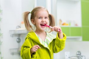young girl smiling brushing her teeth