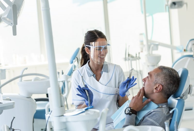 Dentist wearing PPE while talking to patient