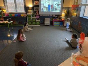 children watching a video about oral health care