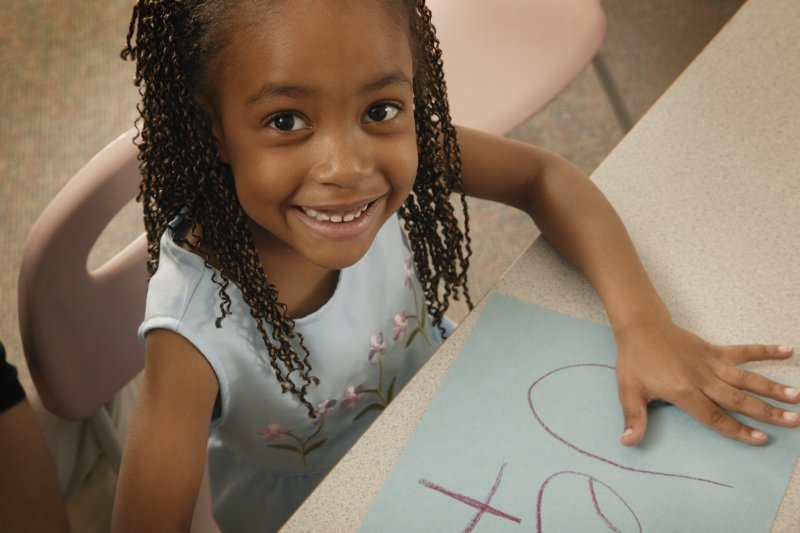young girl in school coloring a picture